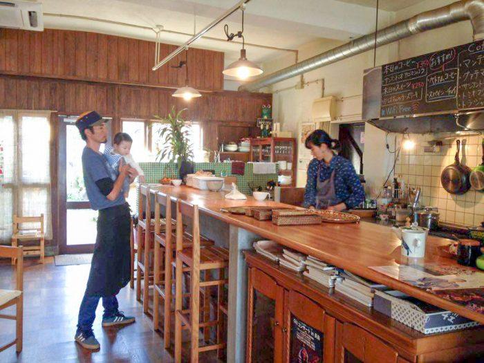 カフェ「ハモニカン」の店内。働く寿乃さんと、次男を抱っこする薫久さん。
